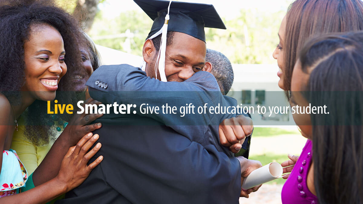 Graduating student hugs his family after graduation, after a Parent Loan helped pay for college